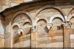 Double jeu d'arcs de l'abside: l'arc supérieur repose sur les chapiteaux sculptés des pilastres semi-engagés, les petits arcs inférieurs  sur modillons sculptés
