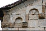 Moulure courant sous le toit et modillons décorés de motifs géométriques, tête de bovidé et tête humaine aux oreilles décollées