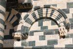 Premier arc composé de bandeaux sculptés en plat relief ( fleurs et cordelette) reposant sur des consoles décorées en haut relief d'un homme et d'un quadrupède en marche
