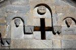 Détail du fronton occidental: au milieu, disque orné d'une croix sur fond végétal,  deux têtes humaines;  à droite: couple de têtes et cheval