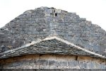 Moulure en calcaire blanc sous la toiture et croix ajourée dans le fronton