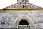 Façade ouest: croix ajourée et arc à claveaux au-dessus de la porte