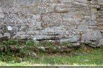 Soubassement de pierres plates pour combler les irrégularités du terrain (mur nord)