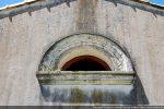 Ouverture semi-circulaire faisant penser à l'arc à claveaux roman; moulure en stuc du 19e siècle