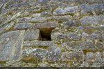 Trou de charpente ménagé entre les pierres et encadré de petits blocs