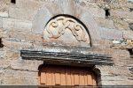Détail de la partie supérieure de la porte: un arc de décharge encadre un tympan monolithe; le linteau mouluré repose sur deux corbeaux gravés