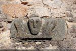 Bloc du 10e siècle: tête entourée de deux mains levées