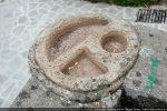 Dessus de la cuve baptismale (les visages se trouvent du côté du demi-cercle)