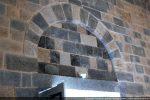 Arc à claveaux, tympan nu et linteau surmontant la porte occidentale