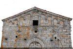 Partie supérieure de la façade avec  trois têtes sculptées de part et d'autre de l'arc en plein cintre