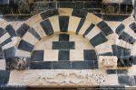 Arc central à claveaux plats, souligné par une bande ornée de fleurettes et de cercles; deux quadrupèdes se font face sur les consoles. Linteau orné de paons disposés de part et d'autre d'une figure humaine (reconstitution). Dans le tympan nu, des pierres évoquent une croix