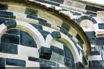 Frise du fronton est: motifs floraux  exécutés avec précision et netteté de gravure; bandeau de l'abside: motifs plus naïfs et en léger relief, sans doute un remploi d'un édifice antérieur. <br class='autobr' /> Sur le fronton, alvéole d'un bol polychrome disparu