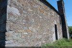 Mur sud percé d'une porte et d'une fenêtre et flanqué au 17e siècle d'un campanile