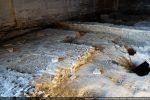Sol médiéval dans lequel se profile la base d'un pilier; à droite: une tombe recouverte de grandes tuiles