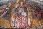 Le Christ, représenté dans une mandorle, est entouré de Jean-Baptiste et de la Vierge
