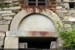 Détail des éléments surmontant la porte : linteau monolithe, arc en plein cintre au tympan nu